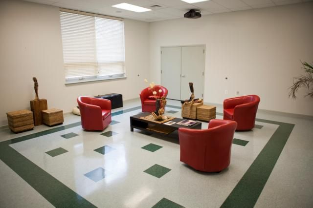 Beckett Gardens community room with 4 large red chairs and a low table